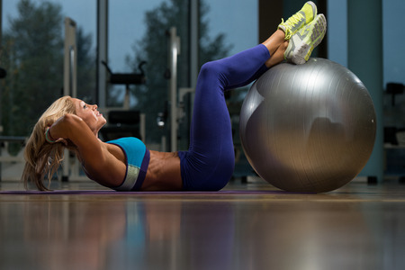 woman middle age: Middle Age Woman Exercising Abdominals On Exercise Ball In Fitness Club