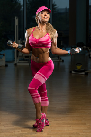 only the biceps: Mature Woman Working Out Biceps In Fitness Center - Dumbbell Concentration Curls Stock Photo