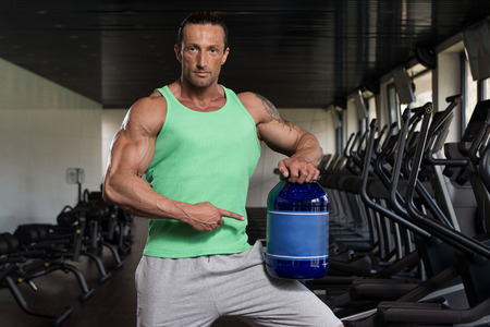 body builder: Muscular Handsome Bodybuilder With Pills And Dope For Copy Space Stock Photo