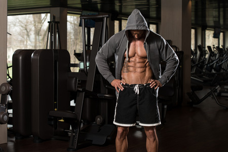 hombre fuerte: Retrato de un hombre f�sicamente Fit En capucha - En Moderno gimnasio - Muestra Su Six Pack
