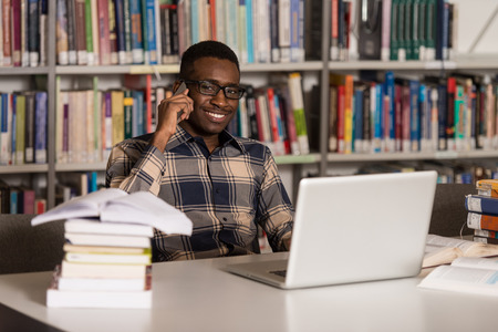 male  beauty: African Male Student Talking On The Phone In Library - Shallow Depth Of Field