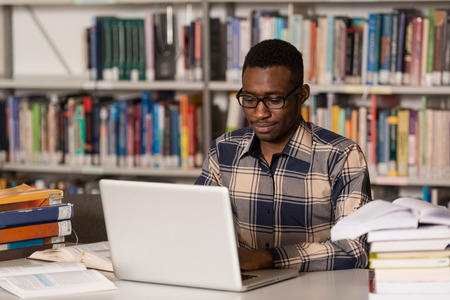 library: In The Library - Handsome African Male Student With Laptop And Books Working In A High School - University Library - Shallow Depth Of Field