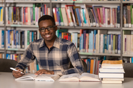 writing black: Portrait Of African Clever Student With Open Book Reading It In College Library - Shallow Depth Of Field