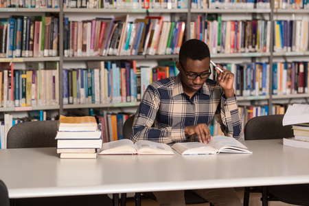 library: Retrato de �frica Clever Estudiante con el libro abierto de lectura en la universidad Biblioteca - Profundidad De Campo Foto de archivo