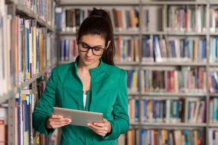 biblioteca: En La Biblioteca - estudiante bastante femenina con la tableta y libros de trabajo en una escuela secundaria - Biblioteca Universitaria - Profundidad De Campo