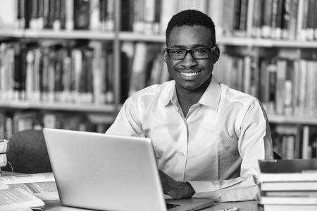 bonhomme blanc: Dans La Biblioth�que - Handsome �tudiant Homme africain avec ordinateur portable et Livres de travail dans une �cole secondaire - Biblioth�que de l'Universit� - la profondeur de champ Banque d'images
