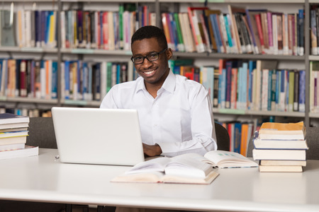 In The Library - Handsome African Male Student With Laptop And Books Working In A High School - University Library - Shallow Depth Of Field