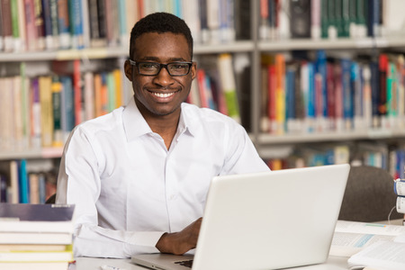 school library: In The Library - Handsome African Male Student With Laptop And Books Working In A High School - University Library - Shallow Depth Of Field