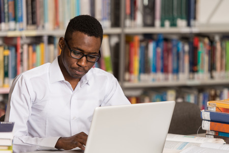 student in library: In The Library - Handsome African Male Student With Laptop And Books Working In A High School - University Library - Shallow Depth Of Field