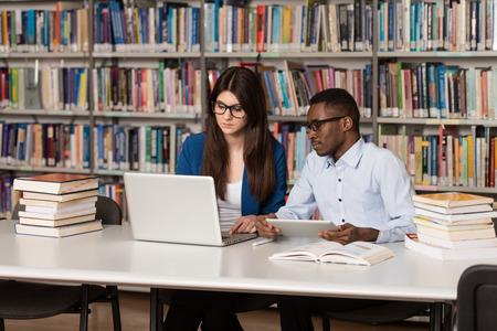 biblioteca: En La Biblioteca - Hermoso Estudiantes Dos universidad con portátiles y libros en una escuela secundaria - Biblioteca Universitaria - Profundidad De Campo