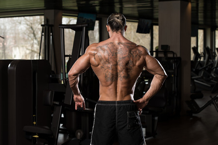 physically fit: Portrait Of A Physically Fit Man In Modern Fitness Center - Showing Back Poses Stock Photo