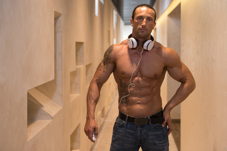 well build: Muscular Mature Man Listening Music From His Mp3 Player In Modern Corridor Where He Poses Stock Photo