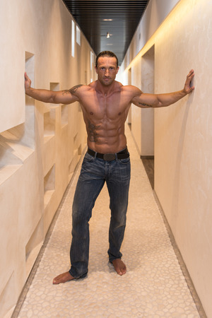 well build: Portrait Of A Muscular Mature Man In The Modern Corridor Where He Poses