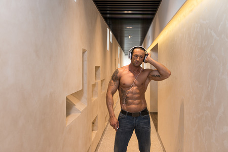 Muscular Mature Man Listening Music From His Mp3 Player In Modern Corridor Where He Poses Reklamní fotografie