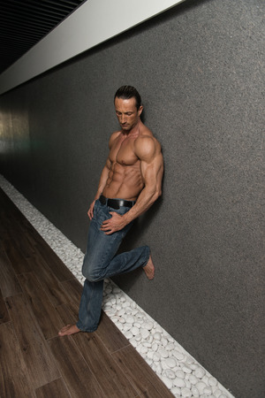 Portrait Of A Muscular Mature Man In The Modern Corridor Where He Poses