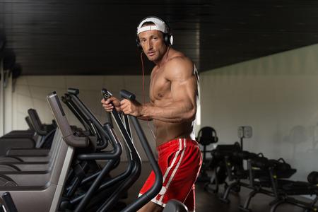 eliptica: Muscular hombre maduro Aer�bic Haciendo El�ptica Walker En moderno gimnasio