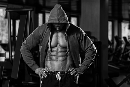 fitness hombres: Retrato de un hombre f�sicamente Fit En capucha - En Moderno gimnasio - Muestra Su Six Pack - Blanco Y Negro Foto