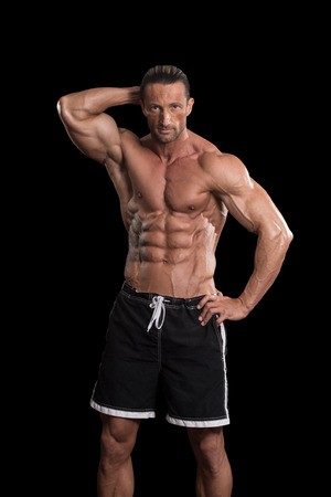 pectorals: Muscular Mature Man Posing In Studio - Isolated On Black Background
