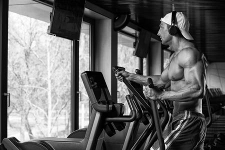 elliptical: Muscular Mature Man Doing Aerobics Elliptical Walker In Modern Fitness Center