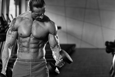 Muskulös Älterer Mann tun Heavy Weight Übung für Bizeps mit Hanteln in einem modernen Fitnesscenter