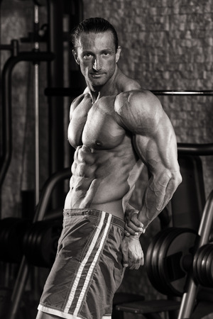 flexing: Mature Man Standing In Modern Fitness Center And Flexing Muscles