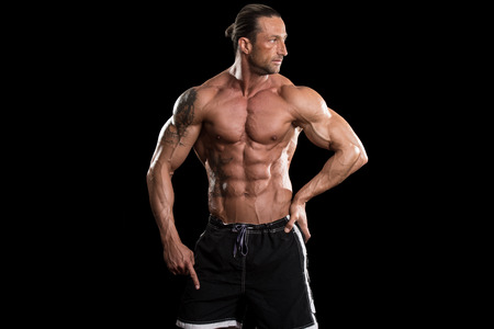 tatouage sexy: Musculaire homme d'âge mûr posant en studio - isolé sur fond noir Banque d'images
