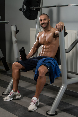 water power: Muscular Man Resting After Exercise And Drinking From Shaker Stock Photo