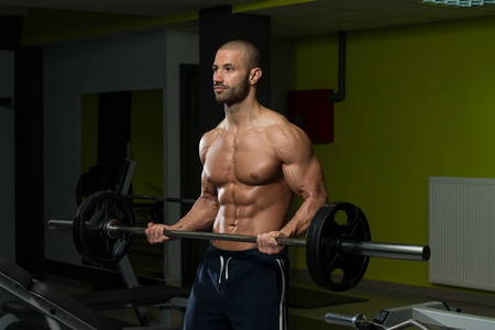 muscle building: Muscular Young Man Doing Heavy Weight Exercise For Biceps In Gym