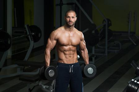 culturista: Bodybuilder que se resuelve Biceps - flexiones de concentraci�n con mancuernas