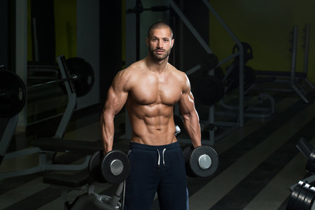 Bodybuilder Working Out Biceps - Dumbbell Concentration Curls Stock Photo