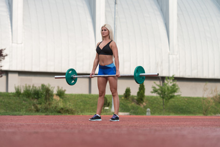 chubby girl: Young Woman Doing A Dead Lift Exercise Outdoor