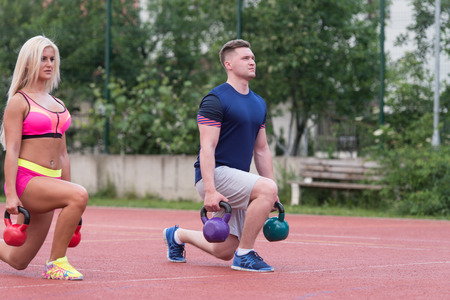group fitness: A Group Of Young People In Aerobics Class Doing A Kettle Bell Exercise Outdoor