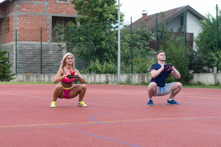 big woman: A Group Of Young People In Aerobics Class Doing A Kettle Bell Exercise Outdoor