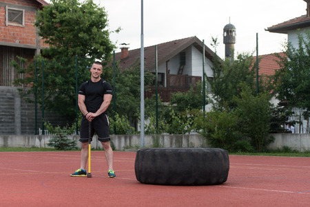 physically fit: Portrait Of A Physically Fit Young Man With Hammer And Tire Resting After Exercise Stock Photo