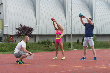 personal trainer: Group Of Young People Doing A Kettle Bell Exercise Outdoor With Instructor