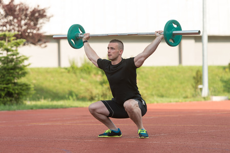 squat: Overhead Squat Exercise Outdoor Performing By A Young Man Stock Photo