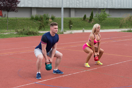aerobics class: A Group Of Young People In Aerobics Class Doing A Kettle Bell Exercise Outdoor