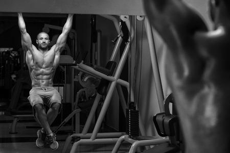 musculo: Hombre joven que realiza Hanging Eleva la pierna Ejercicio - Uno de los ejercicios más eficaz Ab