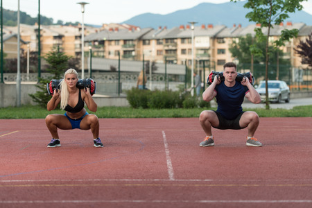 aerobics class: A Group Of Young People In Aerobics Class Performing Bag Squat Exercise Outdoor Stock Photo