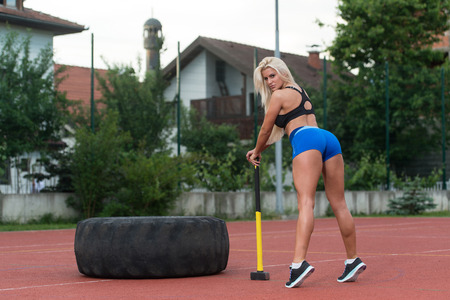 physically fit: Portrait Of A Physically Fit Young Woman With Hammer And Tire Resting After Exercise