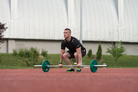 Young Man Doing A Dead Lift Exercise Outdoor Stock Photo