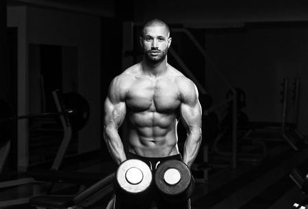 abdominal fitness: Muscular hombre joven que hace Heavy Weight ejercicio para hombros en gimnasia