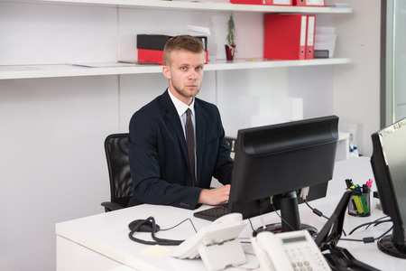 finance manager: Happy Young Business Man Work In Modern Office On Computer