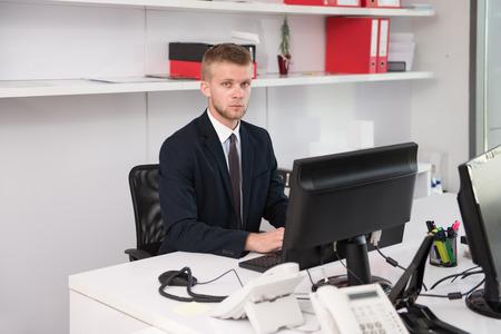 ejecutivo en oficina: Hombre de negocios feliz joven trabajo en la oficina moderna en el ordenador