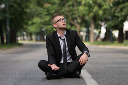 begs: Young Businessman Sitting on Asphalt Begs For Money Outdoors In Park Stock Photo