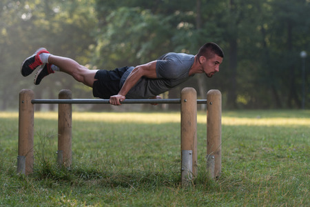 muscular build: Handsome Muscular Young Man Workout In The Park Stock Photo