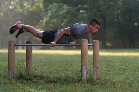 musculoso: Hermoso Entrenamiento muscular del hombre joven en el parque Foto de archivo