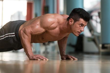 bodybuilder: Joven atleta adulto haciendo flexiones como parte del entrenamiento de musculación