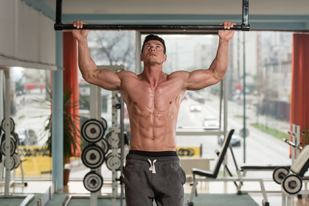 body building: Young Male Athlete Doing Pull Ups - Chin-Ups In The Gym Stock Photo