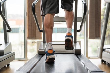 treadmill: Close Up Of Male Legs Running On Treadmill - Blurred Motion
